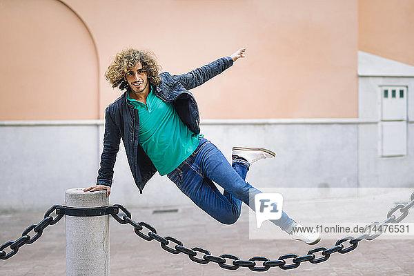 Porträt eines lächelnden jungen Mannes  der im Freien über eine Kette springt