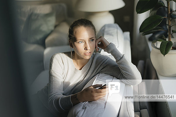 Serious teenage girl with cell phone sitting on couch at home