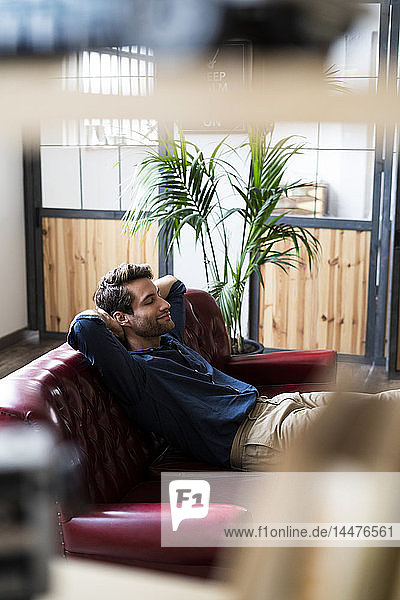 Young man sitting on couch with closed eyes