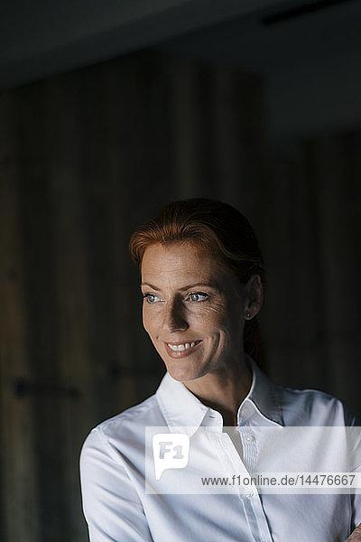 Porträt einer lächelnden Geschäftsfrau  die zur Seite schaut