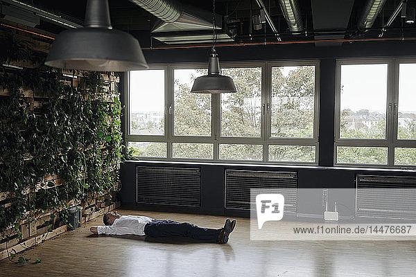 Geschäftsmann im grünen Büro auf dem Boden liegend