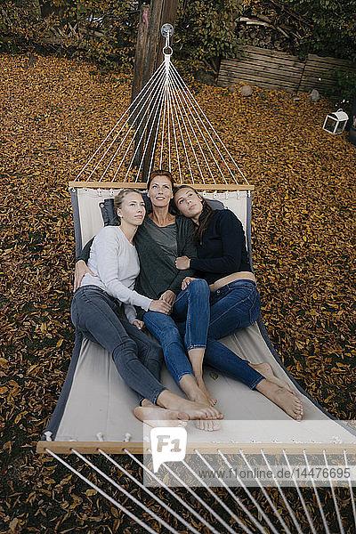 Mutter mit zwei jugendlichen Mädchen,  die im Herbst in der Hängematte im Garten liegen