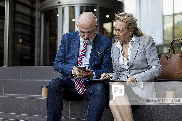Senior businessman and businesswoman sitting on stairs using cell phone and tablet