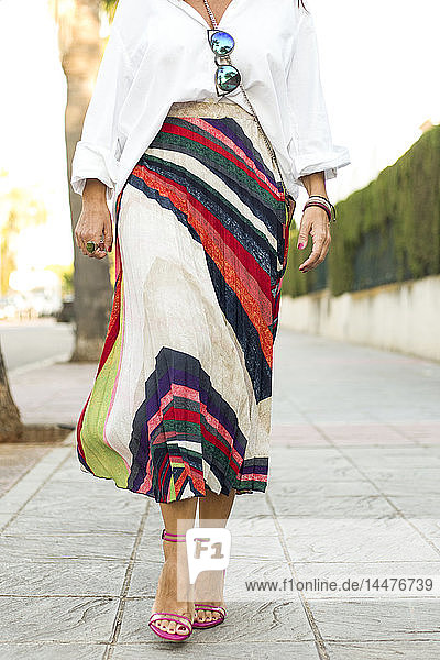Low section of fashionable woman walking on pavement