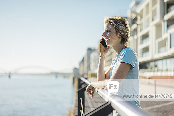 Young woman standing at the riverside  enjoying the sun  talking on the phone