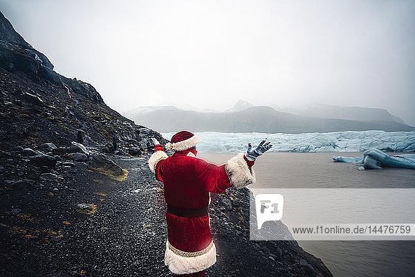 Island  Rückenansicht des vor dem Gletscher stehenden Weihnachtsmanns