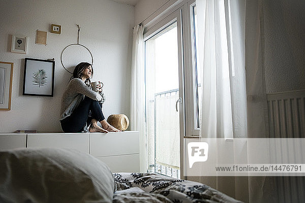 Woman sitting on chest of drawers  drinking tea  relaxing