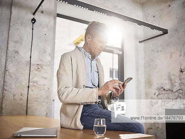 Geschäftsmann sitzt im Büro auf dem Schreibtisch mit Handy und Ohrstöpseln