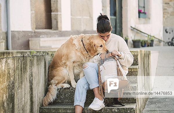 Junge Frau mit ihrem Golden-Retriever-Hund auf der Treppe  im Rucksack