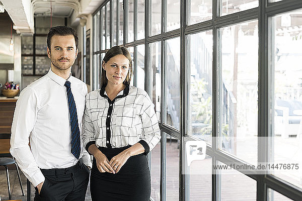 Portrait of two colleagues in front of window