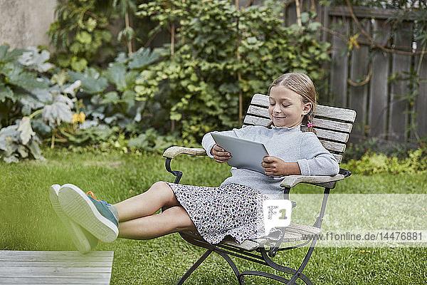 Smiling girl using tablet in garden