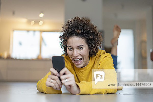 Aufgeregte Frau liegt zu Hause auf dem Boden und benutzt ihr Handy