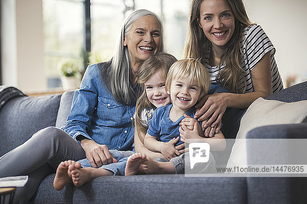 Grandmother and mother sitting on couch with children