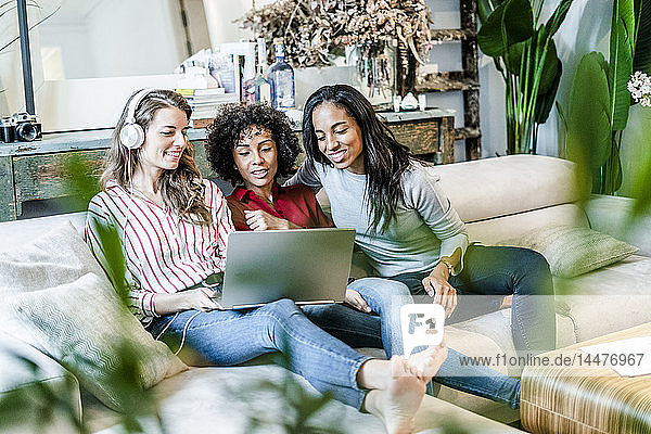 Three happy women with laptop sitting on couch