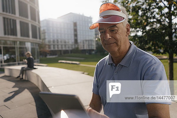 Deutschland,  Hamburg,  Hafencity,  Senioren-Tourist mit Sonnenblende mit Tablette in der Stadt