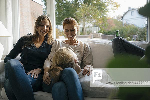Glückliche Mutter mit zwei Teenager-Mädchen auf der Couch zu Hause