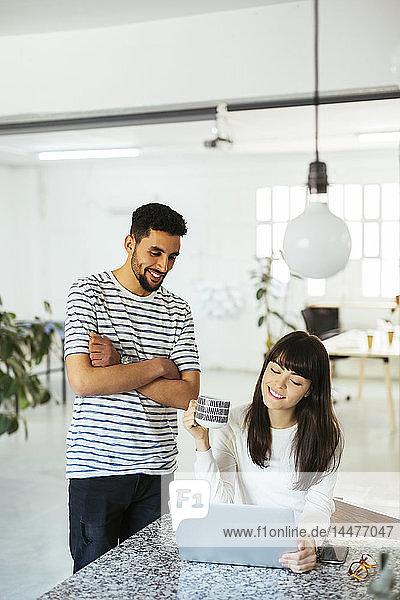 Zwei lächelnde Kollegen arbeiten gemeinsam am Tisch mit Laptop
