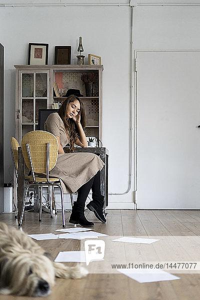 Junge Frau sitzt an ihrem Schreibtisch und denkt nach