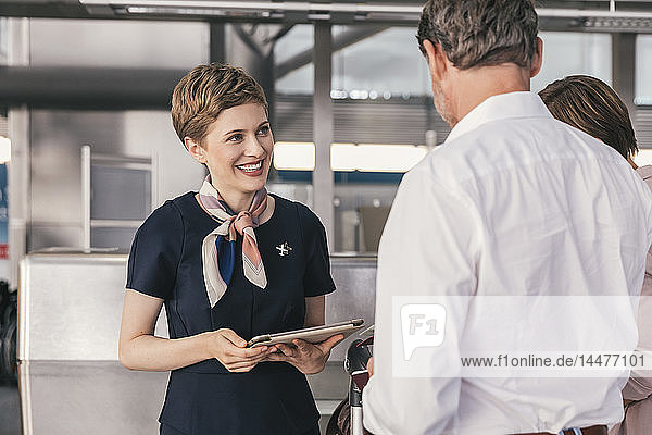 Smiling airline employee talking to couple at the airport