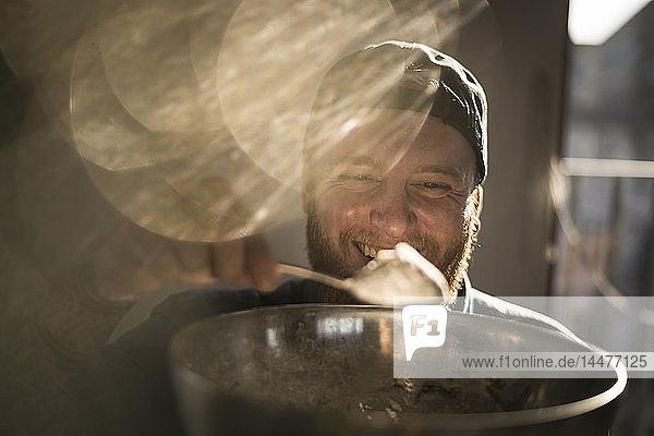 Lachender Mann hält Schüssel in der Küche und fügt seinem Teig Zutaten hinzu