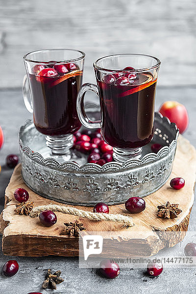 Two glasses of Mulled Wine with cranberries  orange slices and star anise on tray