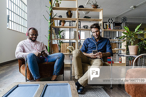 Two young men with cell phones and headphones sitting in armchairs in a loft