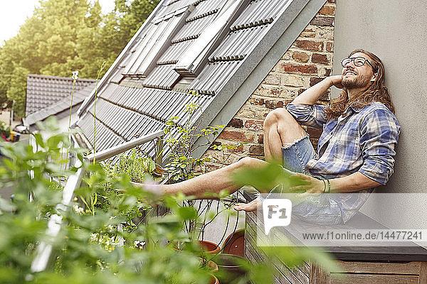 Glücklicher junger Mann sitzt auf seinem Balkon und entspannt Glücklicher junger Mann sitzt auf seinem Balkon und entspannt