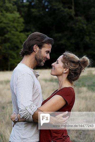 Glückliches Paar in der Natur  von Angesicht zu Angesicht stehend  sich streichelnd