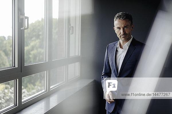 Porträt eines selbstbewussten Geschäftsmannes am Fenster