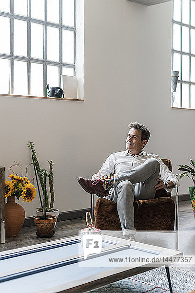 Mature man sitting on chair in a loft thinking