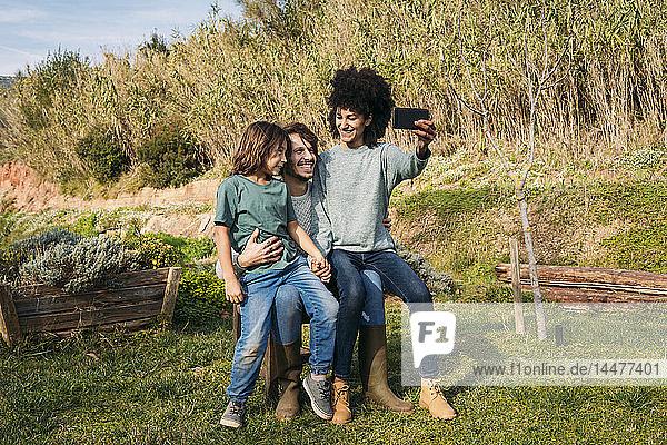 Glückliche Familie sitzt auf einer Bank in einem Garten  die Mutter nimmt sich