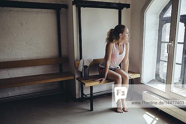 Woman sitting in locker room looking out of window