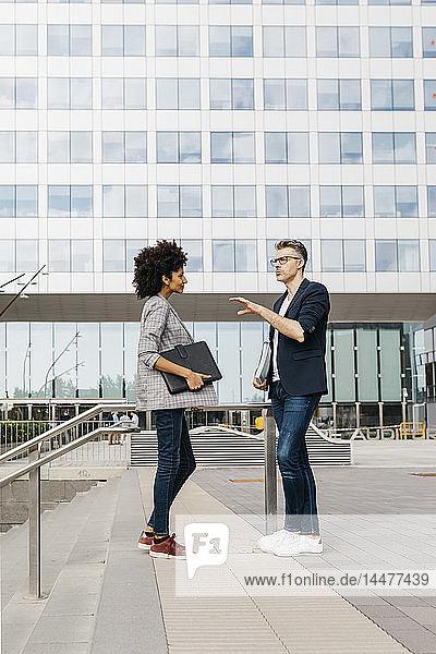 Zwei Kollegen im Gespräch vor dem Bürogebäude