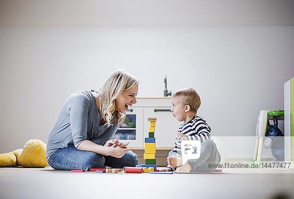 Happy mother and toddler son playing with building blocks at home