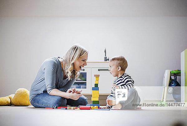Glückliche Mutter und Kleinkind spielen zu Hause mit Bauklötzen