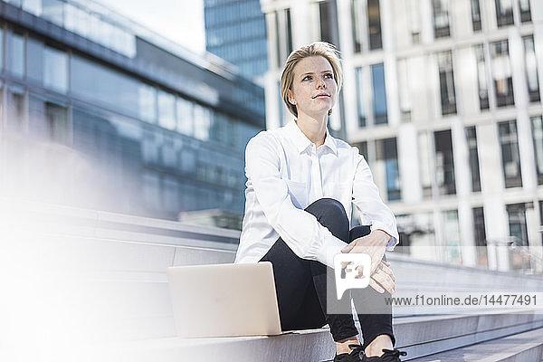 Junger Geschäftsmann mit Laptop  auf einer Treppe sitzend