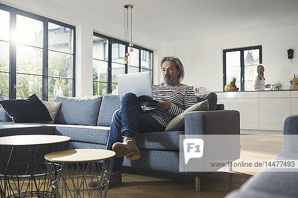 Älterer Mann sitzt auf der Couch und benutzt einen Laptop