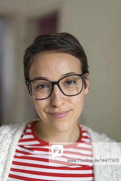 Porträt einer lächelnden jungen Frau mit kurzen Haaren  die eine Brille trägt