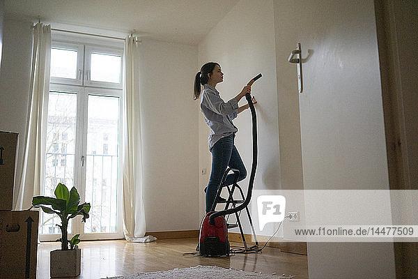 Junge Frau steht auf Trittleiter und staubsaugt ihr neues Zuhause