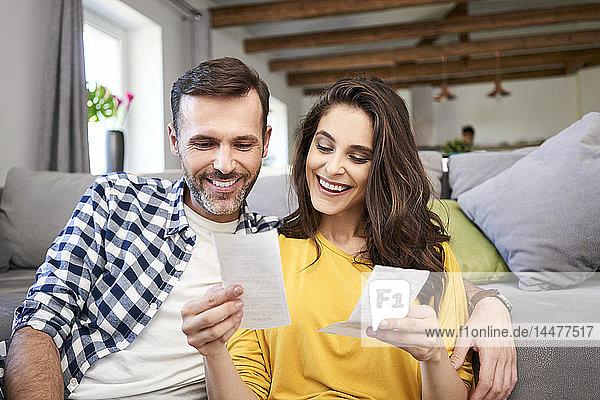 Ehepaar sitzt im Wohnzimmer und kontrolliert Rechnungen