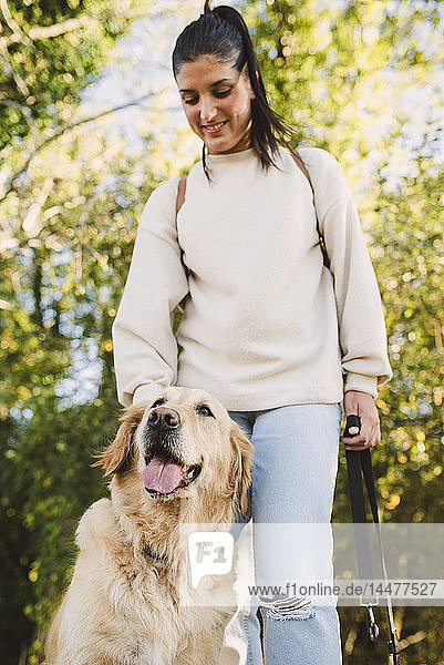 Smiling young woman with her Golden retriever dog in a park