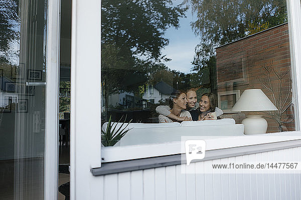 Glückliche Mutter mit zwei Teenager-Mädchen auf der Couch zu Hause hinter der Fensterscheibe