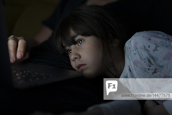 Portrait of daughter watching father using laptop on couch at night