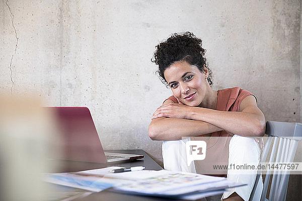 Porträt einer lächelnden Geschäftsfrau  die mit Dokumenten und Laptop am Tisch sitzt
