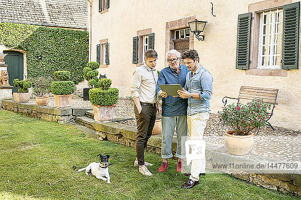 Three men of different age standing in garden using tablet