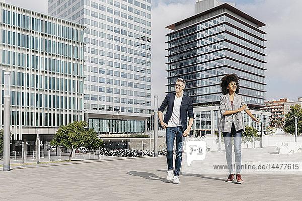 Zwei glückliche Kollegen gehen vor dem Bürogebäude