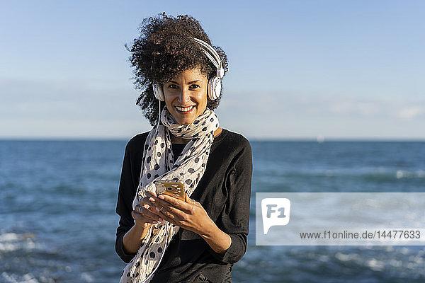 Porträt einer lächelnden Frau  die mit Smartphone und Kopfhörer vor dem Meer Musik hört