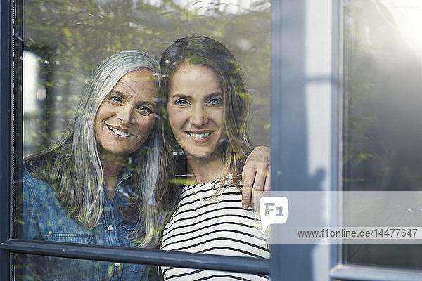 Mutter und Tochter schauen aus dem Fenster