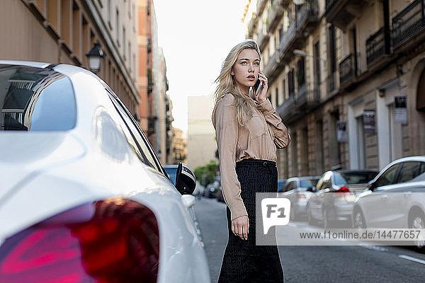 Junge Geschäftsfrau am Handy auf der Straße in der Stadt