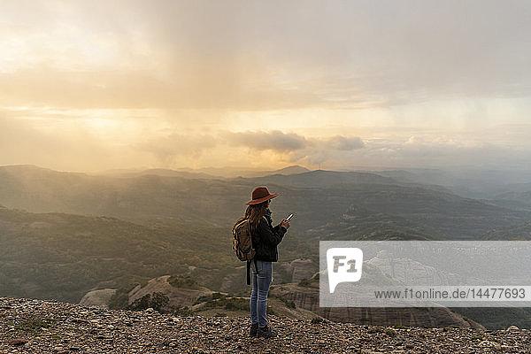 Frau mit Rückenlehne  auf Berg stehend  auf Aussicht schauend  mit Smartphone